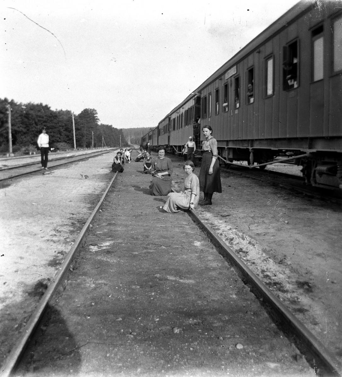 Люди на фоне железнодорожных путях у вагонов
